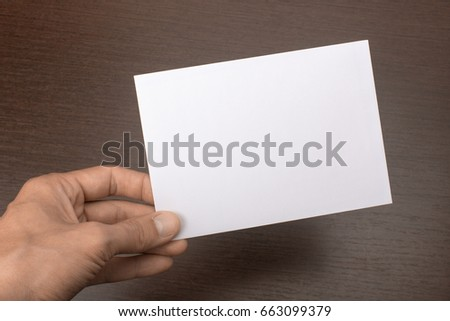 Blank postcard in hand on wooden background. Leaflet A6 mockup