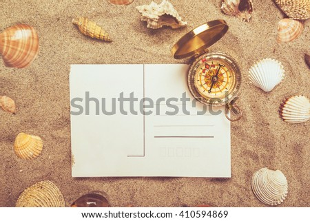 Blank postcard in hot beach sand and magnetic compass with some sea shells, copy space for summer holiday vacation message. - stock photo