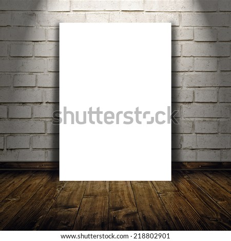 Blank poster as copy space template for your artwork or design in Vintage empty Room interior with white brick brick wall and wooden floor below the spot light.