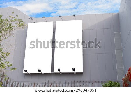 Blank poster board wall in modern shopping mall on a cloudy day. - stock photo