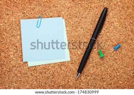 Blank postit notes on cork notice board with pen - stock photo