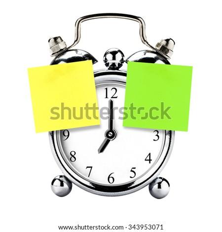 blank Postit yellow green on vintage clock alarm isolated - stock photo