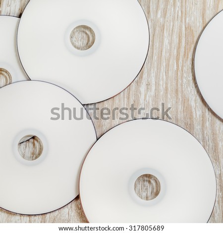 Blank printable CD and DVD on light wooden background. Top view. - stock photo