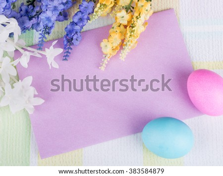 Blank purple envelope with Easter eggs and flowers - stock photo
