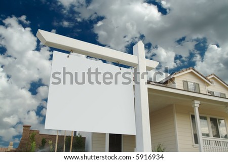 Blank Real Estate Sign in Front of Beautiful New Home - stock photo
