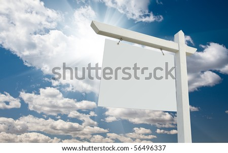 Blank Real Estate Sign over Clouds and Blue Sky with Sun Rays. - stock photo