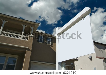 Blank Real Estate Sign with Clouds, Sky and New Home Background - Ready for your own message. - stock photo
