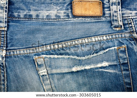 Blank real leather jeans label sewed on old worn blue jeans. - stock photo