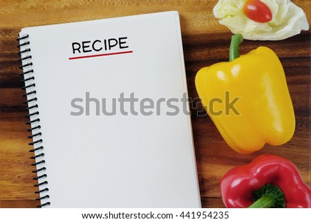 Blank recipe book and vegetable on wooden table background