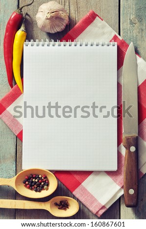 Blank recipe book with kitchen towel on wooden background - stock photo