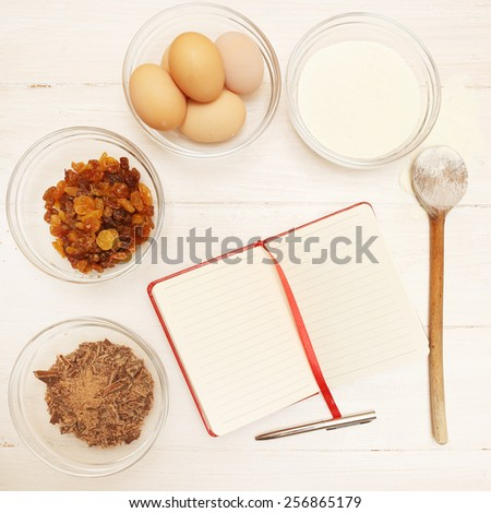 Blank recipe book with various ingredients on the wooden table - stock photo