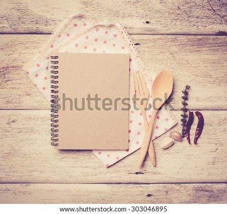 blank recipe book with wooden spoon and fresh herbs and spices on wooden background,vintage color toned image - stock photo