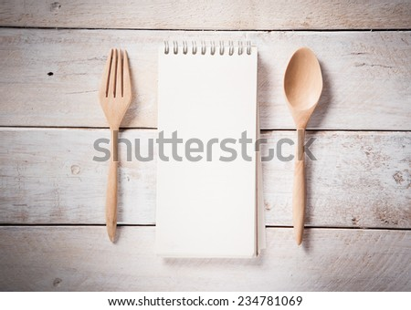 blank recipe book with wooden spoon, vintage toned - stock photo