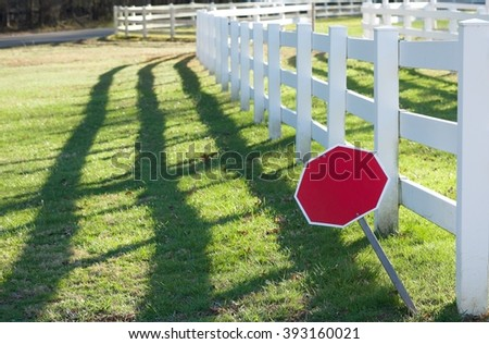 BLANK RED OCTAGON SING IN FRONT OF HORSE FARM WITH WHITE FENCE (BLANK SPACE FOR TEXT)  - stock photo