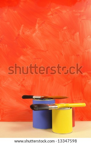Blank red painted wall with paint cans and paintbrushes.  Space for copy. - stock photo