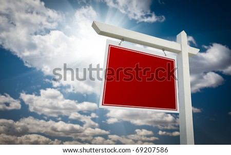 Blank Red Real Estate Sign Over Clouds and Sky Ready For Your Own Message. - stock photo
