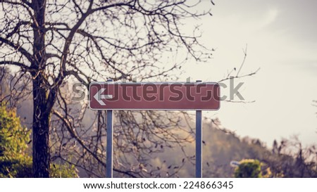 Blank red signpost with left pointing arrow in front of a bare branched deciduous tree with mountain backdrop. - stock photo
