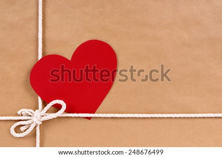 Blank red valentine card or gift tag on a brown paper package background tied with string.  Space for copy. - stock photo