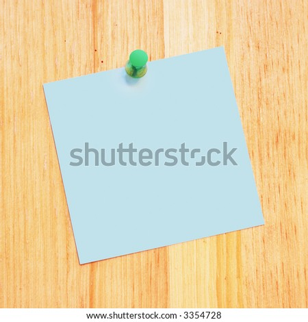 blank reminder on a wood desk with push pin