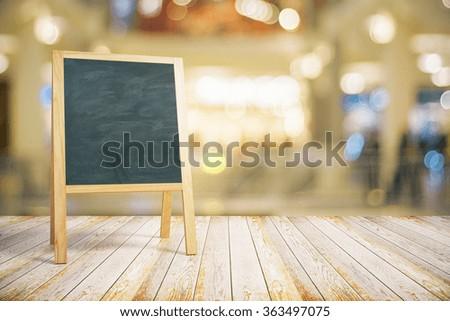 Blank restaurant blackboard on wooden floor, mock up - stock photo