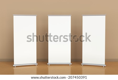 Blank roll-up banners against the brown wall - stock photo