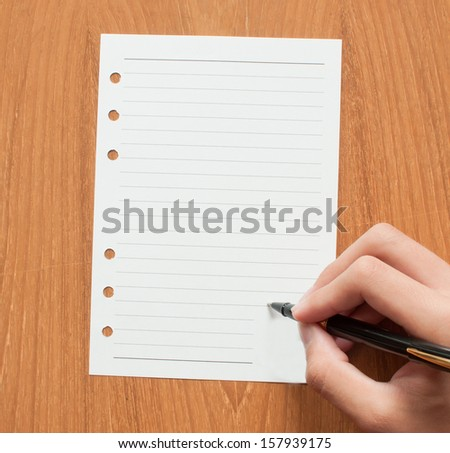 blank ruled school sheet paper with hand and pen, writing - stock photo