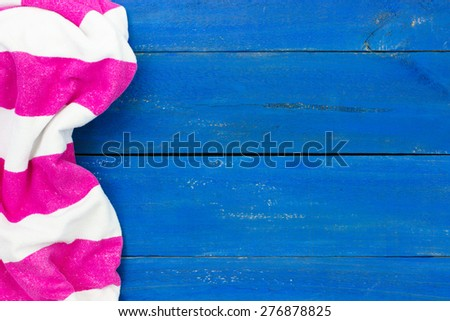 Blank rustic blue wooden beach sign with pink and white striped beach towel - stock photo