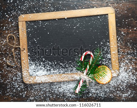 Blank rustic Christmas chalkboard slate with scattered snow and a colourful striped candy cane ready for your seasonal greetings - stock photo
