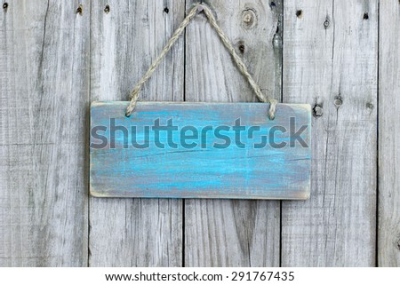 Blank rustic teal blue wooden sign hanging on old weathered wood background - stock photo