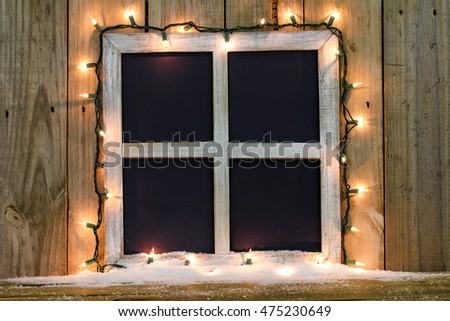 Blank rustic window frame with string of holiday lights and snow by antique rustic wood  background
