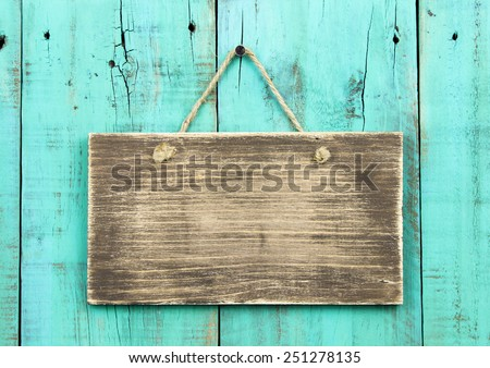 Blank rustic wooden sign hanging on washed out teal blue distressed wood background - stock photo