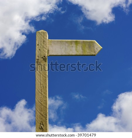 Blank Rustic wooden signpost against blue sky. Add your own text to the sign, includes accurate clipping path to easily change background. - stock photo
