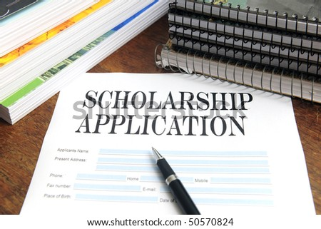 blank scholarship  application on desktop with books - stock photo
