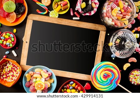 Blank school slate surrounded by a frame of colorful bright assorted candy in bowls and jars, candy canes and rainbow colored spiral lollipops on black - stock photo