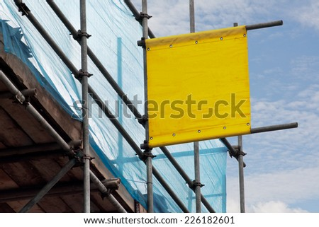 Blank scoffolding sign for advertising a scaffolders business erected on some scaffold a prime vantage point for advertising. - stock photo