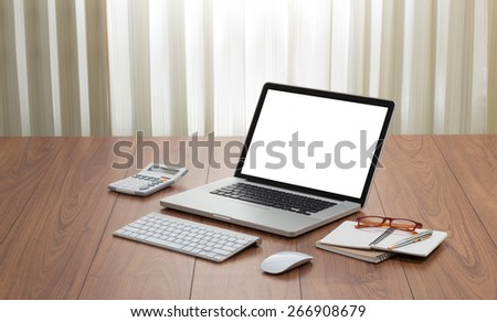 Blank screen laptop computer with office accessories on wooden table - stock photo