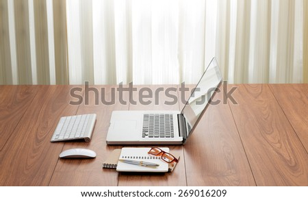 Blank screen laptop computer with office accessories on wooden table