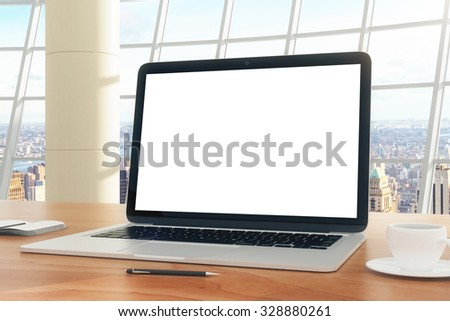 Blank screen of laptop on the table in the office with city view - stock photo