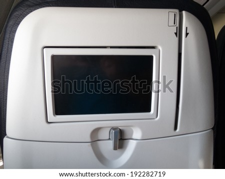Blank screen on the back of an airplane seat - stock photo