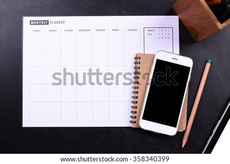 blank screen smartphone with notebook and planner schedule - stock photo