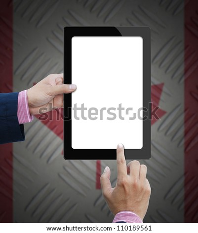 Blank screen tablet computer in business hand on canada flag background.