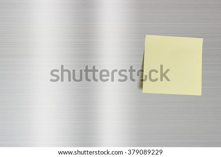 Blank sheet of a light yellow paper on a fridge door. For leaving someone a short note, a message, an order, a memo etc. when you are not at home for a long weekend or getting up or coming back late. - stock photo