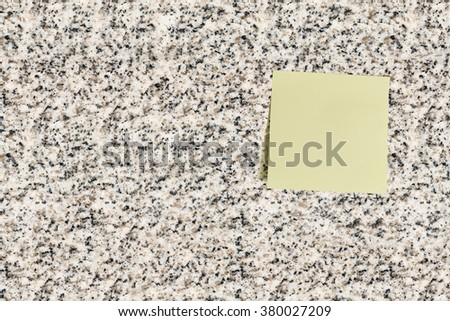 Blank sheet of a light yellow sticky note posts on a granite wall surface. For writing a short memo, hints, alert. warning, stimulation, motivation, words, phrases, cautions, etc to someone at office. - stock photo