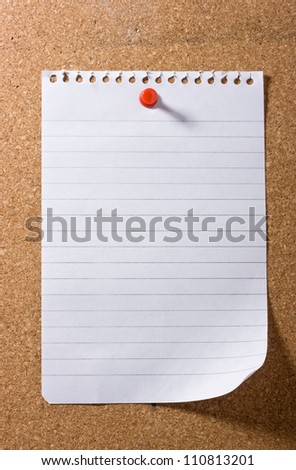Blank sheet of note paper with a curled up corner, pinned to a cork bulletin board with red pushpin casting a long shadow. Ready for your text. - stock photo