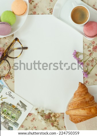 Blank sheet of paper for notes on a flower tablecloth with coffee, macaroon, croissants and postcards in the French style - stock photo