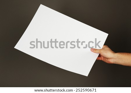Blank sheet of paper in male hand on dark background
