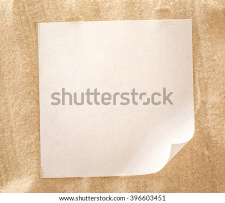 Blank sheet of paper on sand background - stock photo