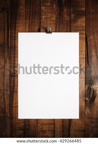 Blank sheet of paper on vintage wooden table background. White paper with plenty of copy space. Blank paperwork template for design portfolios. Top view. - stock photo
