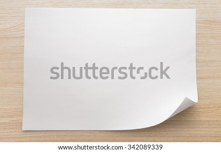 Blank sheet of paper on wooden background in closeup