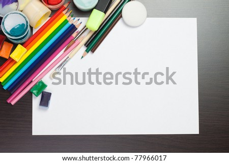 blank sheet of paper with colorful artist instruments creative process